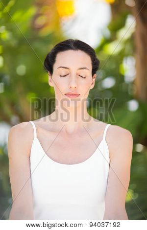 Portrait of a woman in a meditation position against a white background