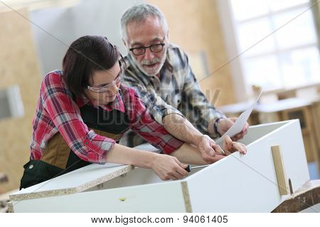 Young woman with senior craftsman in carpentry class poster