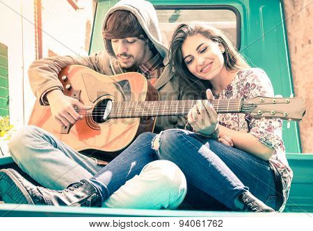 Romantic Couple Of Lovers Playing Guitar On Old Fashioned Mini Car - Nostalgic Retro Concept Of Love