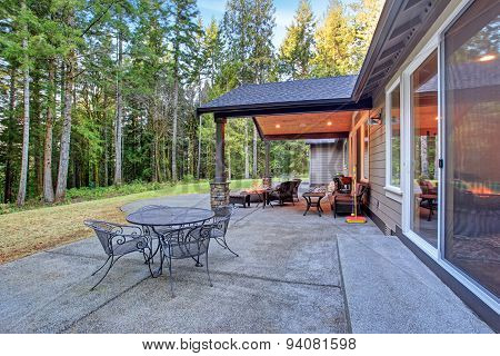 Large back yard with grass and covered patio with firepit. poster
