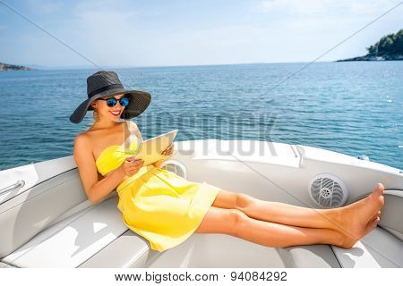 Woman relaxing with digital tablet on the yacht