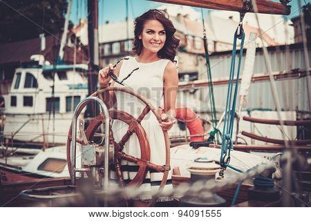 Stylish wealthy woman on a luxury wooden regatta   poster