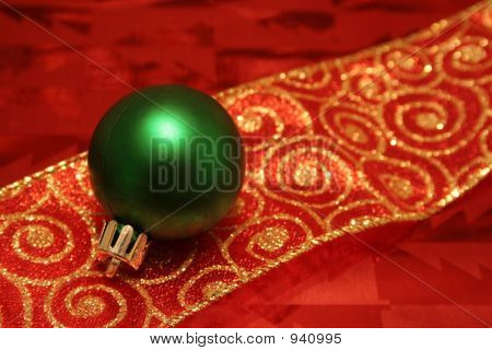 a green christmas ball decoration resting on ribbons and wrapping paper. poster