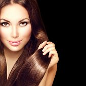 Beauty Model girl with Healthy Brown Hair. Beautiful brunette woman touching long smooth shiny straight hair. Hairstyle. Hair cosmetics, haircare. Hair care, extensions. Isolated on black background poster