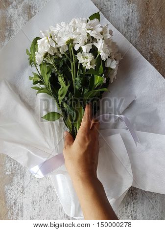 bouquet of white chrysanthemum flowers on a white wooden background