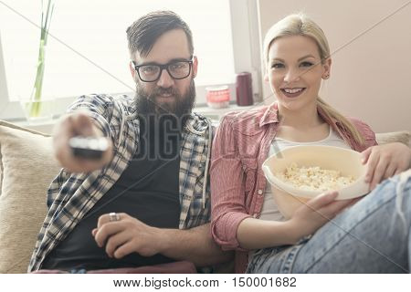 Young couple in love sitting on a couch enjoying the weekend watching TV and eating popcorn. Lens flare effect on the window