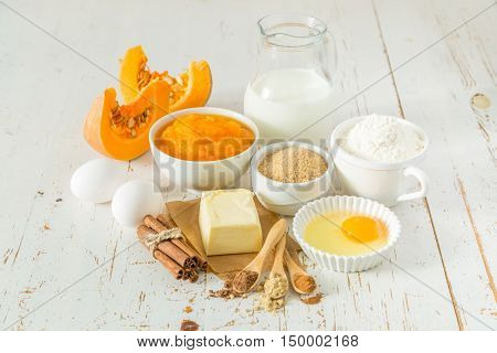 pumpkin pie ingredients in bowls on wood background