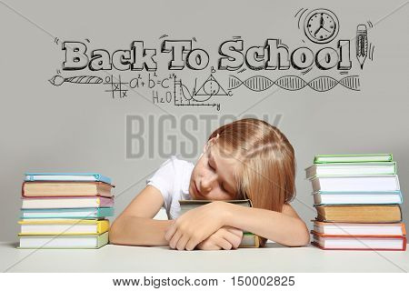 Tired girl lying on stacked books at table. Text BACK TO SCHOOL on gray background. Education concept.