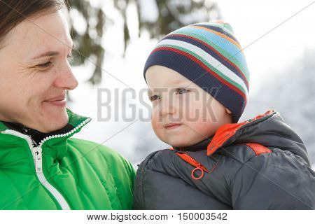 Mother holding her son in a snowy winter landscape bonding having fun smiling talking and enjoying family time. Mothers day family values parents love and happy childhood concept.