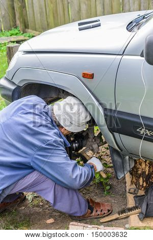 Man repairing the front suspension of the car in the field. Repair their own hands.