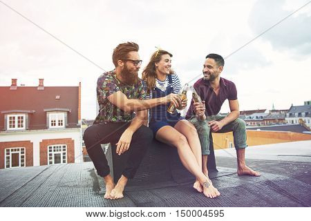 Cheerful group of barefoot adults drinking beer on roof outdoors with copy space in sky