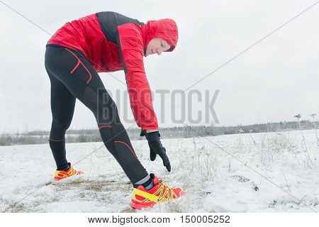 Sportsman during outdoor winter training session at natural snowy field background