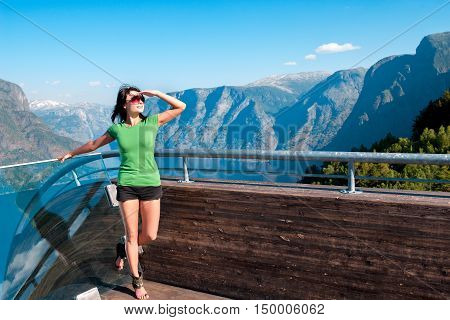 Woman enjoying scenics from Stegastein Viewpoint in a summer sunny day, looking forward with hand on forehead Flam, Norway