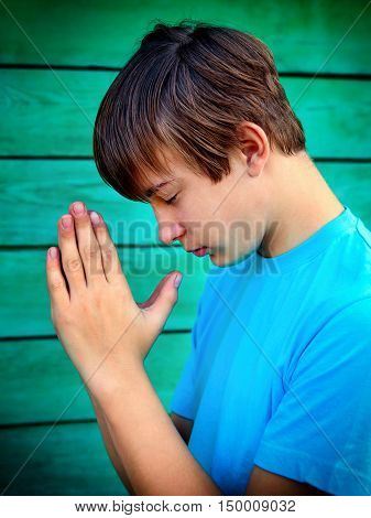 Teenager praying on the Wooden Wall Background