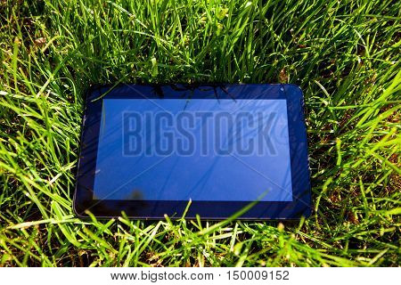 Tablet Computer on the Green Grass closeup