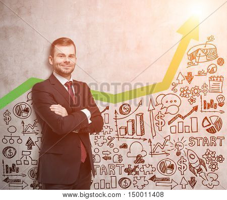 Smiling businessman in red tie standing near concrete wall with green arrow and startup sketch on it. Concept of small business. Mock up. Toned image