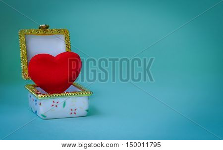 Jewelry box with a red heart inside on blue background