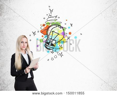 Portrait of blond businesswoman with notebook standing near concrete wall with colorful light bulb sketch. Concept of good idea. Mock up