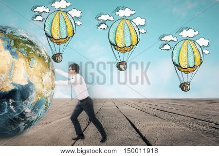 Side view of young businessman pushing the globe against sky themed wall with hot air balloon sketches. Concept of adventure. Toned image
