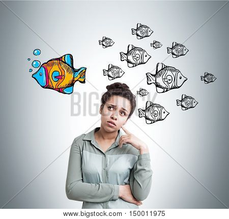 African American woman with thinking against fish sketches on light gray wall. All fish are black and white. One is colored and swimming in different direction. Concept of extraordinary person