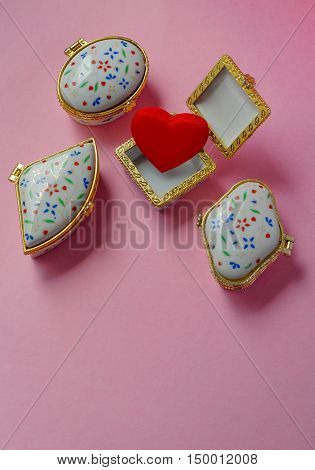 Jewelry boxes with one having a red heart inside on pink background, top view