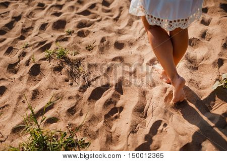 Beach Travel woman walking on a sandy beach leaving footprints in the sand. Close up detail of female legs and golden sand on the beach