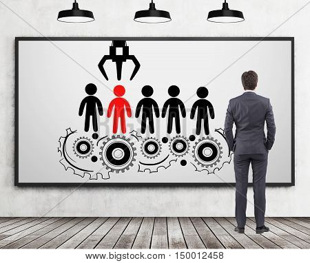 Rear of confident businessman looking at conveyor belt sketch with grabhook picking one person. Concept of hiring in successful company