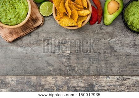 Nachos, guacamole and ingredients on wooden background