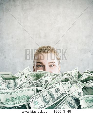CLose up of girl's head half seen behind huge dollar pile in concrete wall room. Mock up