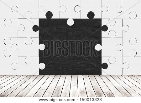 Blank blackboard in room made of puzzle pieces with wooden floor. Concept of missing pieces. Mock up
