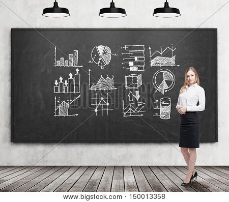 Smiling blond businesswoman standing near blackboard with graphs on it. Concept of statistics in business.