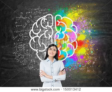 Dreamy girl with black hair standing near blackboard with brain sketches on it. Concept of brain studying