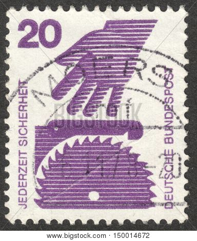 MOSCOW RUSSIA - CIRCA SEPTEMBER 2016: a stamp printed in GERMANY shows a hand and a circular saw (Factory Safety) the series
