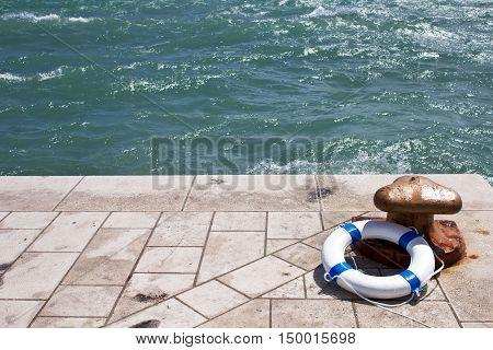 Bollard and lifebuoy lifebelt on a stone pier by the sea