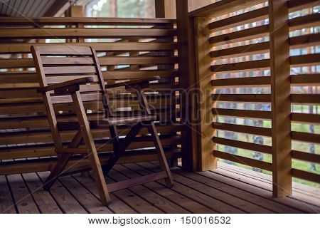 lone wooden chair on the balcony of wood with baffles in autumn day