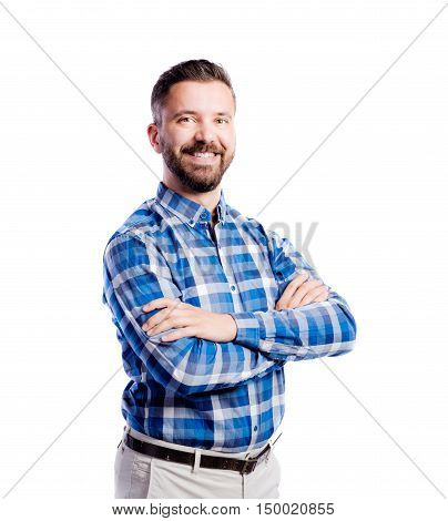 Young handsome hipster man in checked blue shirt, arms crossed, studio shot on white background, isolated