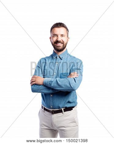 Young handsome hipster man in blue denim shirt, arms crossed, studio shot on white background, isolated