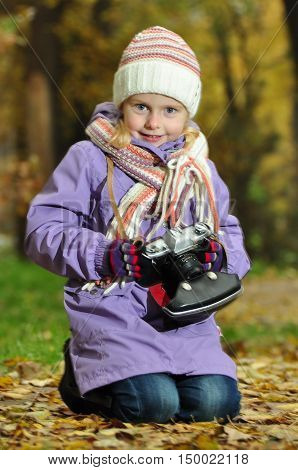 child with camera on nature in autumn