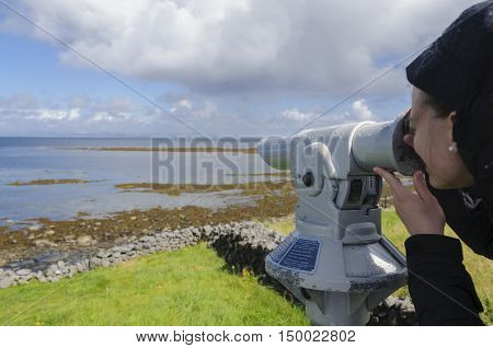 Young girl looking through a coin operated spyglass in Inishmore, Aran Islands, Galway Bay, Ireland, Europe