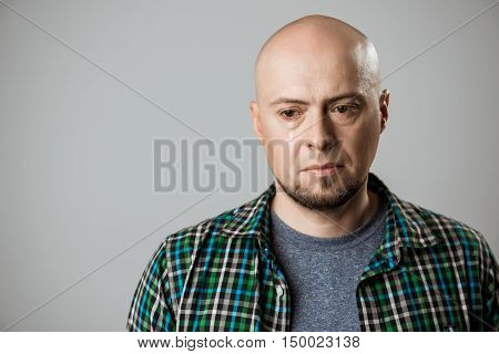 Portrait of upset handsome man thinking over beige background. Copy space.