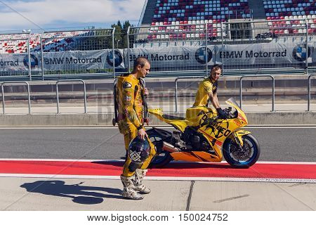 Moscow region, Russia - 27 August : route Moscow raceway rider yellow suit and helmet, and technical personnel to carry the bike around the pits after the race in day of Russian cinema 27 August, 2016.