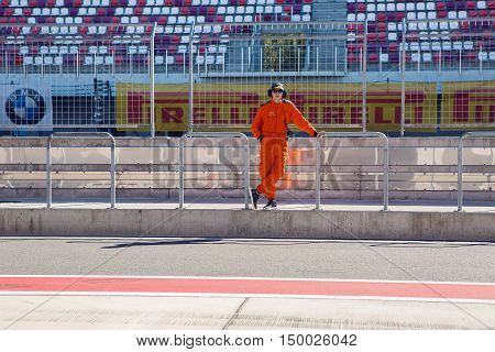 Moscow region, Russia - 27 August : route Moscow raceway technical staff male in an orange jumpsuit , the clothes are on the inner track in day of Russian cinema 27 August, 2016.