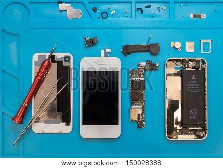 Flat lay image of dismantling the broken smart phone for preparing to repair or replace some components Top view