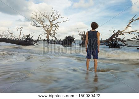 Time exposure of man standing in flood waters from flood tide