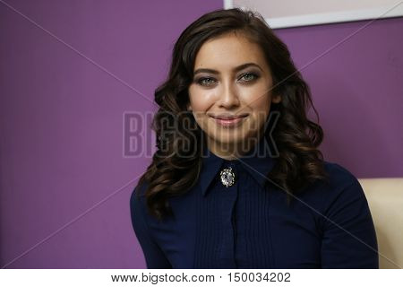 portrait of a beautiful young girl on a bright purple background