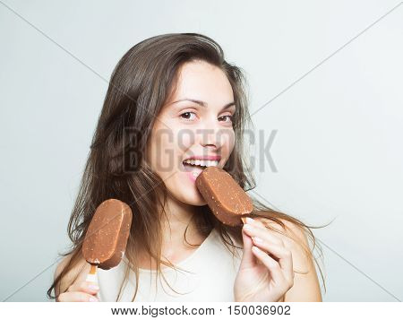 young sexy woman or girl with long brunette hair and pretty smiling happy face eating chocolate ice lolly in white shirt in studio on grey background copy space