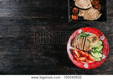 Porkchop baked and served on the plate with fresh vegetable garnish
