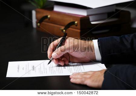 Man signing last will and testament, closeup