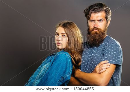 Fashion couple of pretty girl in denim jacket and handsome bearded man hipster in t-shirt pose on grey background