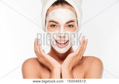 Beautiful smiling woman with white clay facial mask on face isolated on white background
